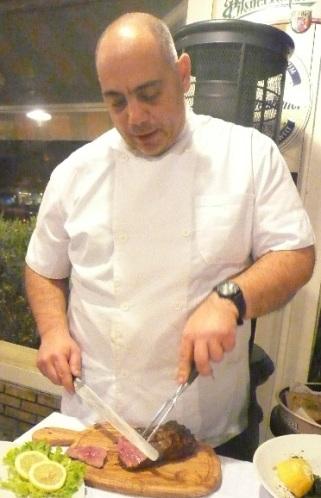 Ο Βαγγέλης κόβει το εσκαλοπ στο τραπέζι στο base grill